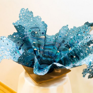 Vase By Linda Turner /  Layers of sculpted organza, thread painted to suggest the splash of water and mounted on a turned wooden base