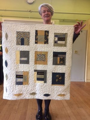 Claire Powell with her quilt made from fabrics from New York