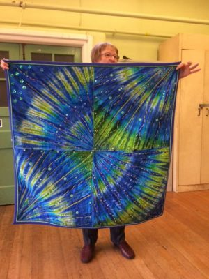 Margaret Currie showing her amazing Blue and green embroidered and beaded quilt